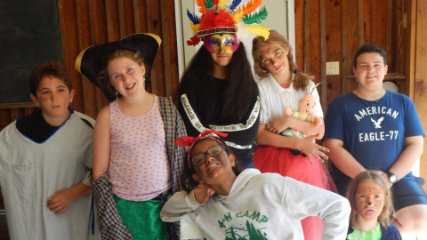 Campers in costume pose together before a drama skit.