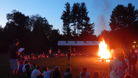 Campers seated in a large circle around a bonfire.
