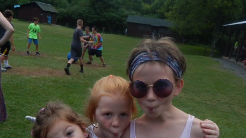 Three campers standing together making fish faces with pursed lips into the camera.