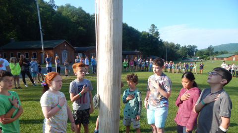 Group of youth saying the pledge of allegiance at the flagpole while the rest of camp follows along from a larger circle.