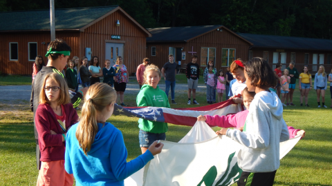Youth work together to fold the American and 4-H flags while the rest of camp looks on.