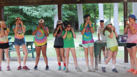 Cabin group wearing tie dye t-shirts and sunglasses flossing their teeth.