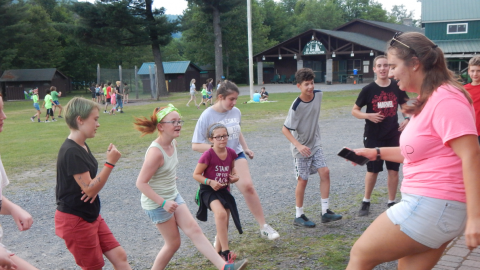 Counselor demonstrates a dance for campers who follow along kicking their feet and laughing.