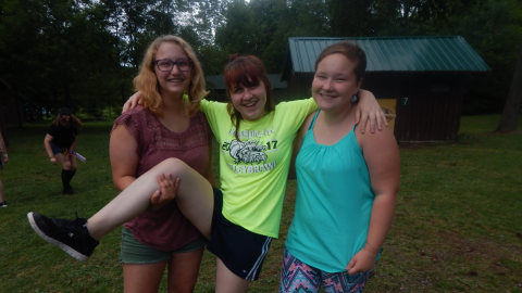 Three campers standing together smiling. One holds up one leg of the middle camper.
