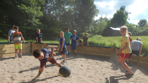 Youth hits a rubber ball in the gaga pit as others scatter behind them so as not to be hit. Players who have been eliminated watch from outside the gaga pit.