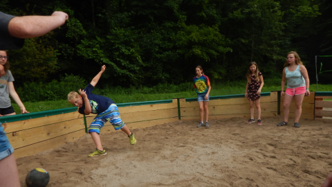 youth in the gaga pit. One youth is leaned far to the side toward a kickball with hands raised behind them and one foot off the ground.