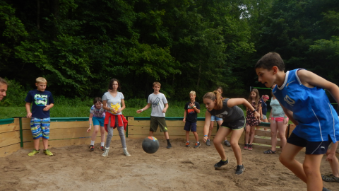 Youth around the edge of the gaga pit while a counselor in the center prepares to hit the ball.