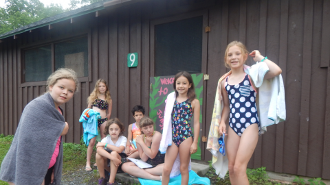 cabinmates sit on stoop of cabin in bathing suits and towels waiting for Polar Bear to be called.