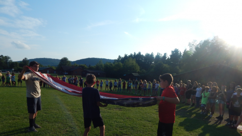 three campers work together to fold the American flag while the rest of camp looks on.