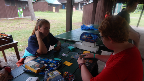 Youth playing Magic card game with counselor.