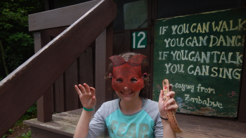 camper seated on cabin 12 porch wearing a mask and holding a crafted bracelet.