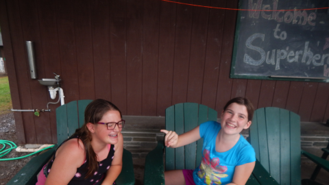 two campers sitting in Adirondack chairs and laughing.