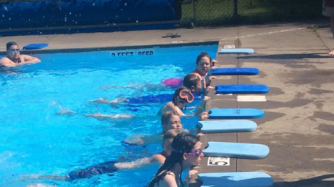 Youth hold the side of the pool with legs outstretched kicking. Each youth has a kickboard in front of them on the pool deck.