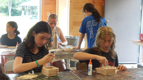 Campers seated at table in craft hall constructing boxes with glue and Popsicle sticks.