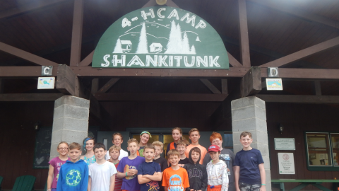 Group of 16 youth gathered together under the camp dining hall sign.