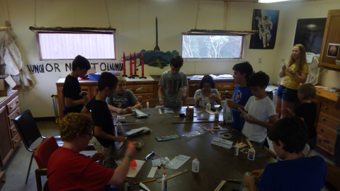youth seated around the table in various stages of building model rockets as counselor looks on with hot glue gun.