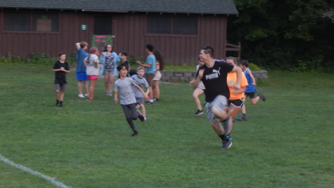 Counselor running from a group of campers who are chasing them.
