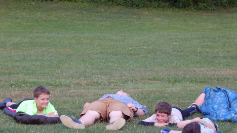Cabin group laying on sleeping bags in the field laughing.