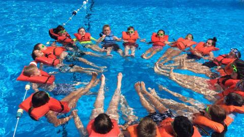 Group of youth in the pool wearing life jackets and linking arms to form an orange rescue circle.