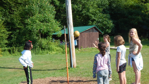 Five youth around a tether ball poll. Three watch while two are playing.