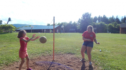 camper playing tether ball with counselor.