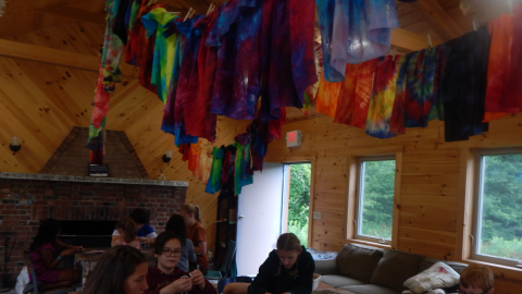 youth working with paracord at a table with colorful tie-dyed bandannas hung over their heads.