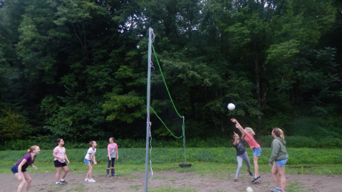 youth playing volleyball. One youth jumps toward the ball on the right side of the net with arms extended after hitting it toward the opposing team of four.