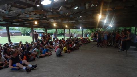 campers seated in the rec pavilion as a group of campers perform a skit.