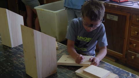 youth wearing goggles while sanding their wood project.